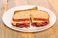 Pastrami sandwich on Jewish Rye bread with swiss cheese, mustard, and kosher dill pickles.