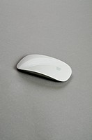 A wireless computer mouse displayed on a grey background.