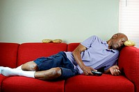A senior citizen sleeping on a couch with a remote control in hand and potatoes on the couch.