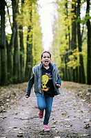 Girl is running shouting into a tree-lined avenue in autumn