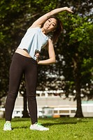 Healthy woman doing stretching exercises in park