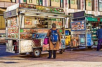 Woman ordering and buying food from a Halal Food Cart, Upper West Side, New York City, Second cart in the background.