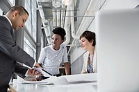 Business people looking at digital tablet in office building
