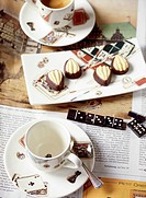 Two coffee cups on newspaper with triangle shape chocolates on plate