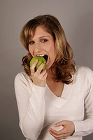 Portrait of young woman biting green apple