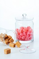 Glass jar filled with square and round shaped candies