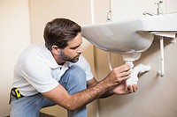Plumber fixing the sink in a bathroom