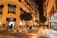Carrer del Convent de Santa Clara pedestrian street with cafe tables at night.