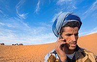 Morocco Sahara Desert sand dunes portrait of local man with turbin on cell phone in Las Palmeras area.