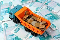 Transportation of small coins for the toy truck. Concept.
