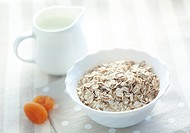 Lifestyle photo of healthy breakfast with oat-flakes and milk