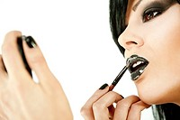 Close-up of beautiful female face with black make-up applying lipbalm