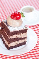 beautiful cake with strawberry and tea on plaid fabric
