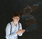 Sneaky business man, student, teacher or politician thinking of evil scheme with missile flag war map on blackboard background North and South Korea