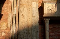 Carvings and artwork around entrance to red brick Romanesque Basilica of Sant Ambrogio, Milan, Lombardy, Italy, Europe.