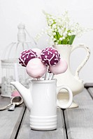 Pastel cake pops on rustic grey wooden table. Bouquet of lilly of the valley flowers in ceramic vase in the background.