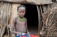 Girl belonging to the Dhasanech tribe in front of a hut ( Omo valley, Ethiopia).