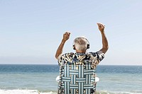 Older man listening to headphones on beach