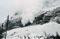 Avalanche of snow crashing down steep mountainside.