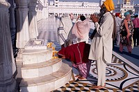 Golden Temple. Barefooted Sikh pilgrims praying at shrine.