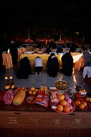 Morning prayers in the main prayer hall. Kneeling worshippers with table in foreground spread with offerings of fruit flowers and candles.