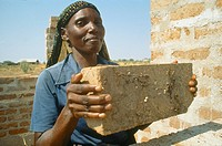 Woman in Mshikimano squatter settlement taught to make bricks for building her house.