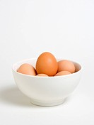 Free range eggs in a bowl on a white background.