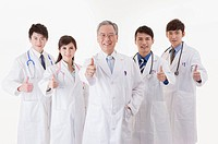 Healthcare workers standing and smiling at the camera with thumbs up together