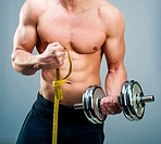 muscular man measuring his biceps with dumbbells