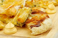 Slices of Cheese and Greens Puff Pastry Pie Garnished with Cheese Sauce closeup on Cutting Board