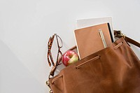 Studio Shot of shoulder bag with apple and notebook in it