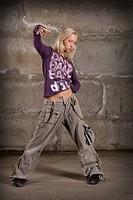Beautiful hip hop girl dancing over grey brick wall