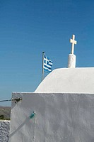 greek flag behind a white chapel, isolated on blue sky