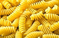 pile of fusilli pasta close up on wood background