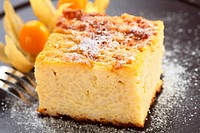 Baked rice pudding dessert sweetened with sugar powder and garnished with physalis in the back with a fork on the side (Very Shallow Depth of Field, F...