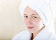 A woman smiles wearing a bathrobe and towel.