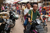 Pedestrians and motorcycle riders on the street in Luh Market; Siem Reap, Cambodia