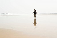 Young woman walking on the beach from HuoHu, North of Kinmen Island; Taiwan
