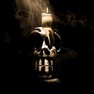 Dark still life photo of a carved wooden skull with a melted candling casting a pagan spell to release the souls of the dead.