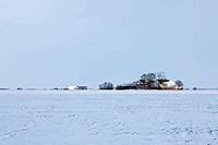 White winter landscape of field with farm