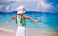 Back view of beautiful little girl spread her arms on an exotic beach