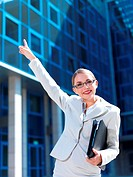 Friendly businesswoman pointing to the office