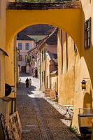 Cobblestone street with souvenir shops and tourists in the medieval town of Sighisoara, Romania, Eastern Europe.