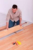 Labourer slotting together laminate flooring