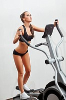Sexy young sportswoman exercising on simulator