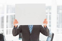 Businessman holding placard over his face