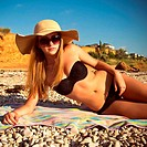 Girl on the beach wearing a straw hat