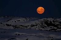 huge moon in the night sky over one of the Antarctic islands