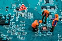 Miniature engineers fixing error on chip of motherboard