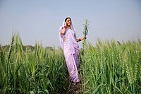 Low angle view of Indian female farm worker talking on mobile phone